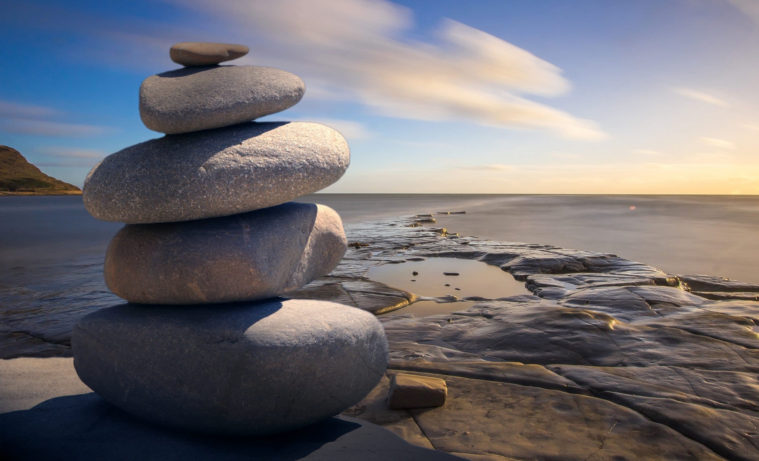 Pedras equilibradas em frente a uma praia.
