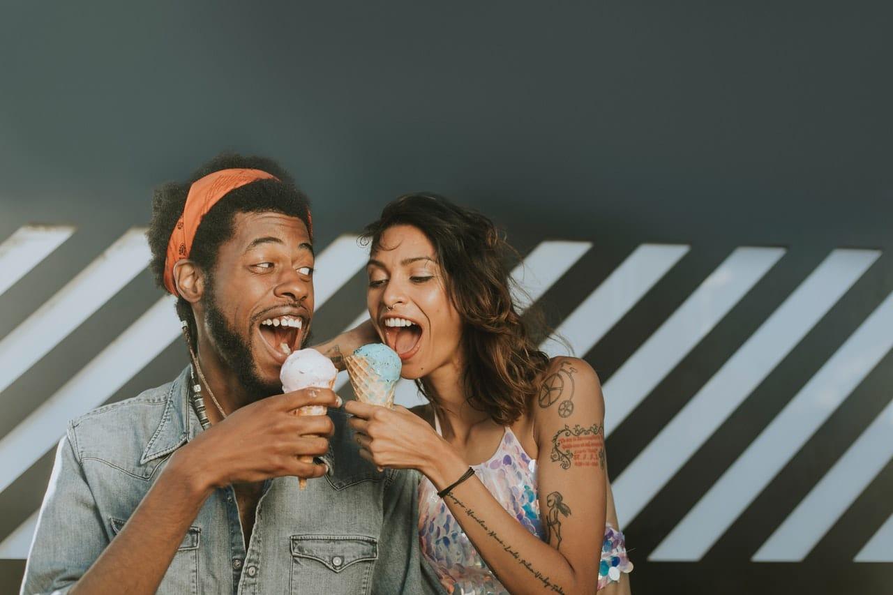 Casal com sorvete de casquinha na mão com boca aberta para morder