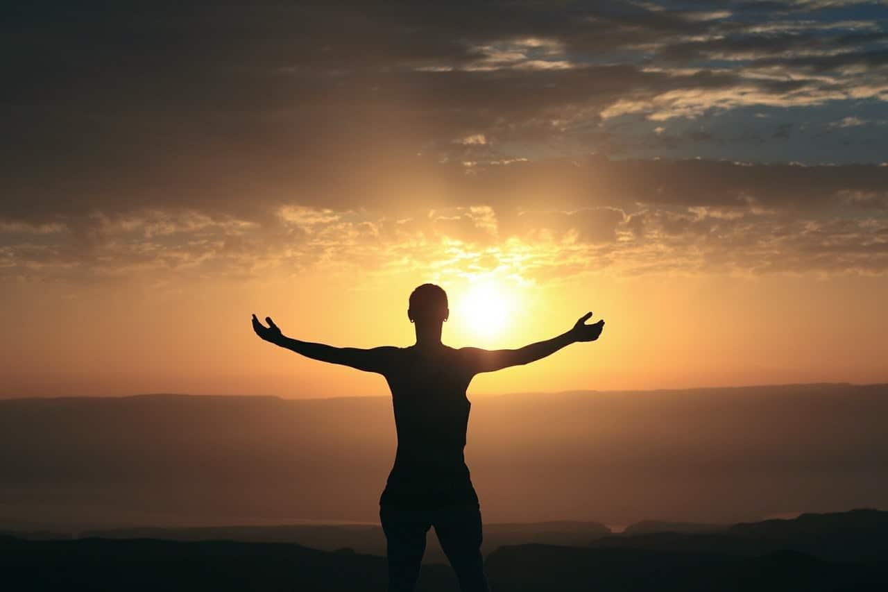 Silhueta de pessoa de costas com braços abertos e céu e pôr-do-sol ao fundo