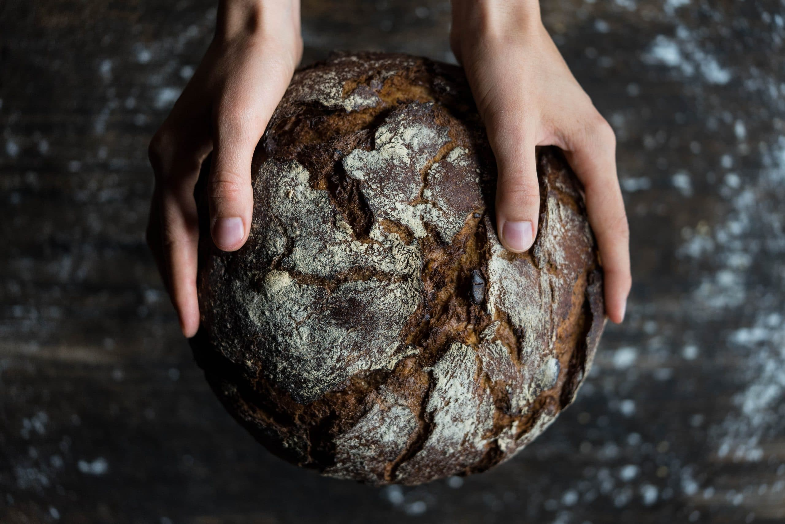 Mãos segurando uma pedra com relevos que se assemelham à representação do globo terrestre.