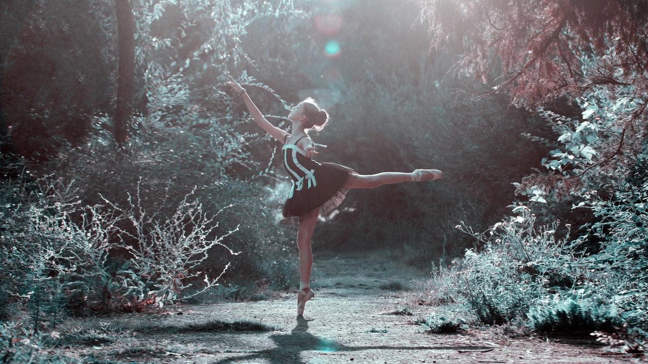 Bailarina em ponta de pé em floresta iluminada