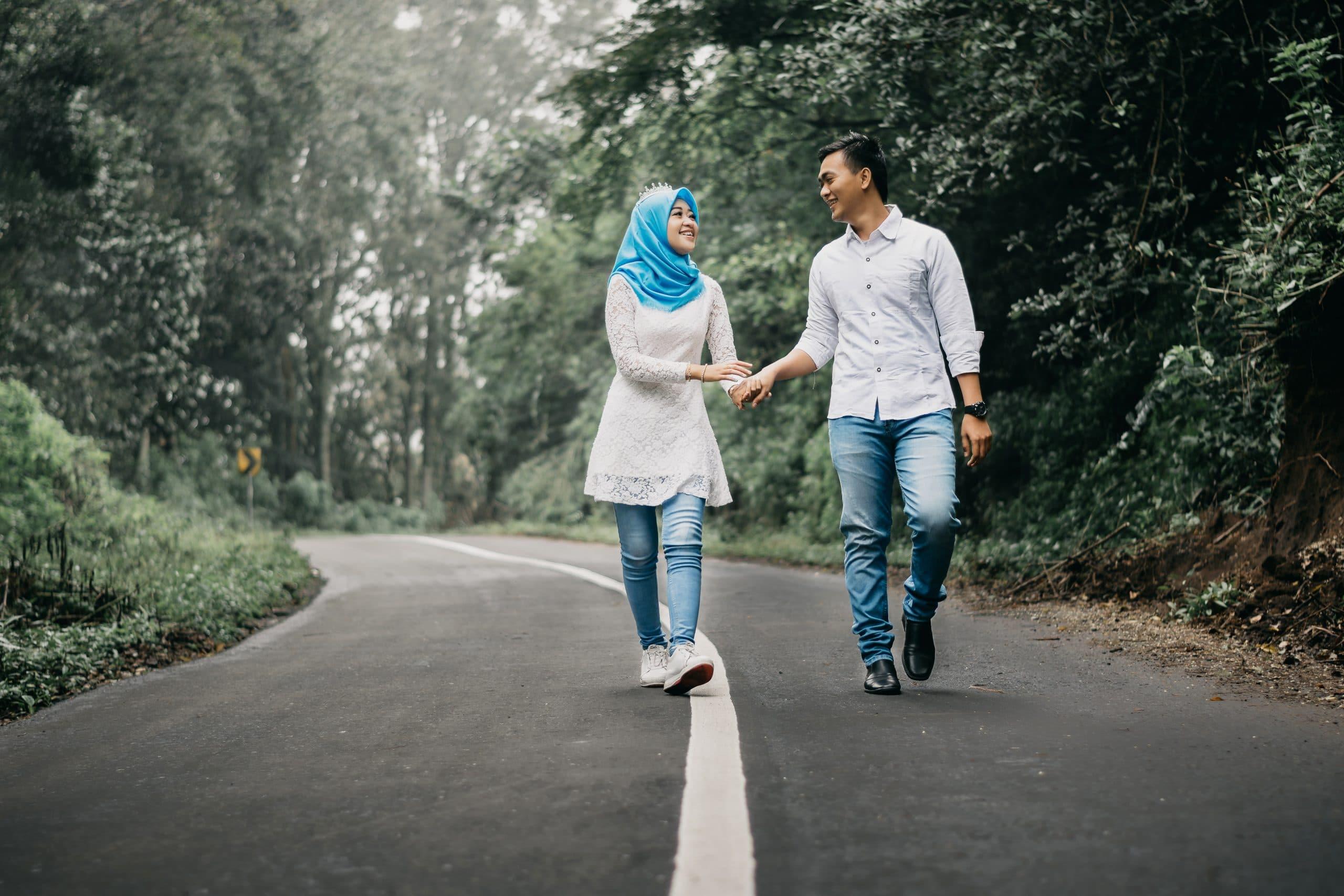 Duas pessoas se cumprimentando no meio de uma estrada. Uma delas usa uma burca.