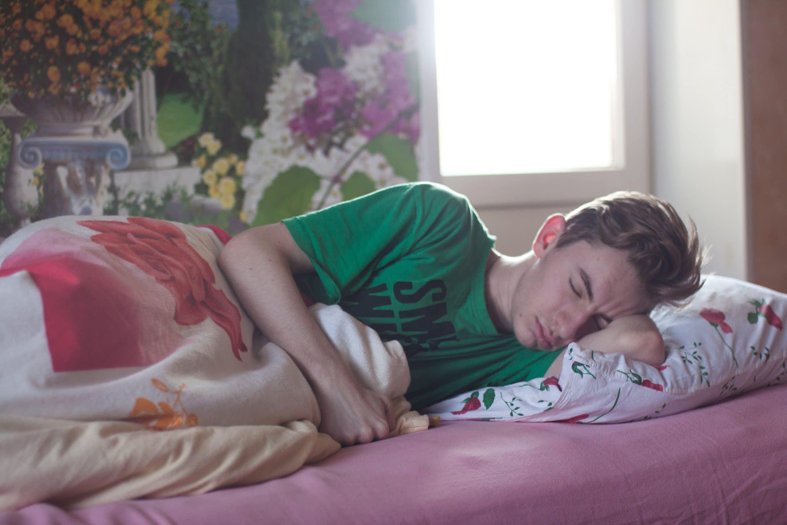 Menino dormindo na cama em um quarto sonhando com a expressão angustiada.