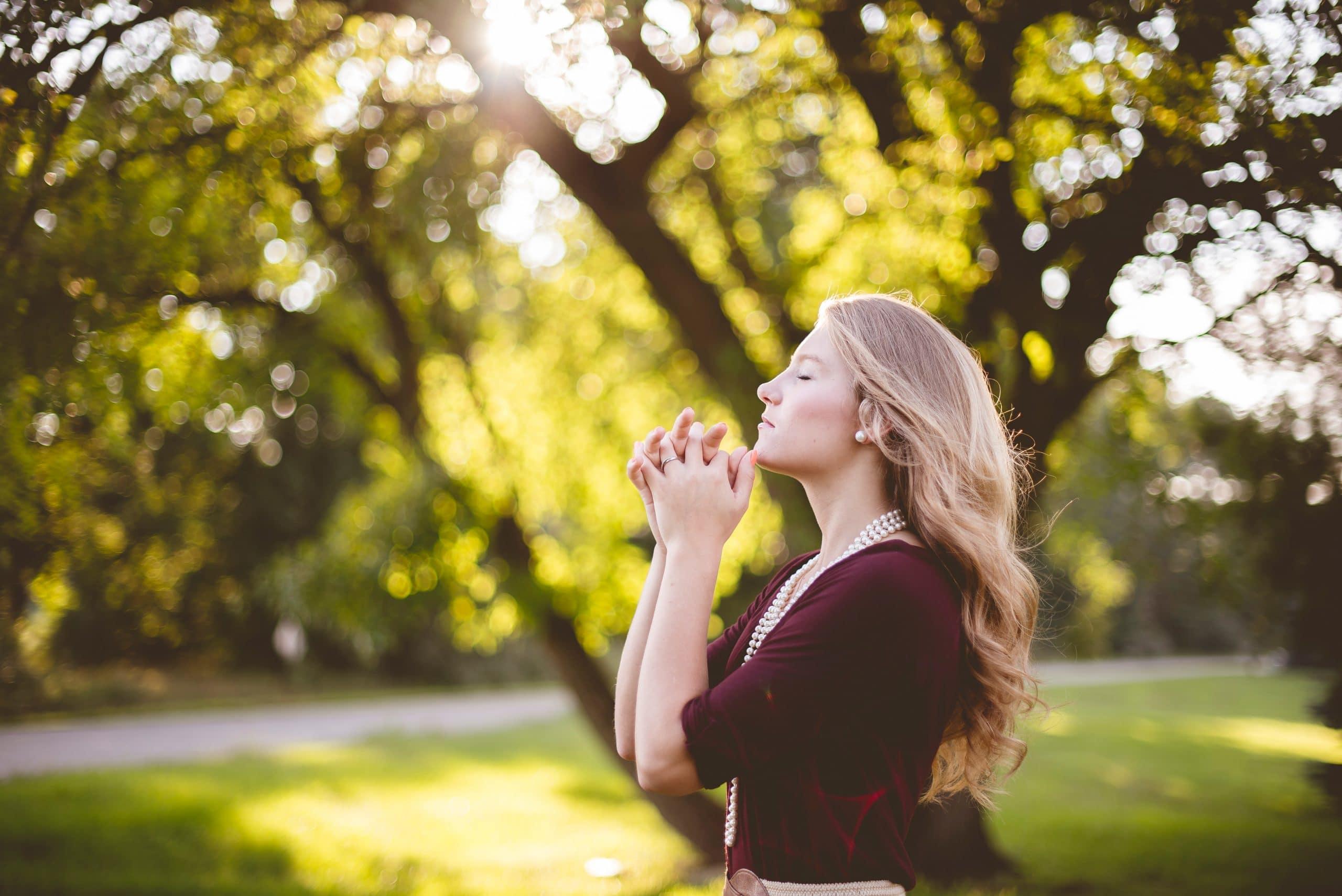 Mulher com as mãos unidas em sinal de oração em meio a um parque. Seus olhos estão fechados.