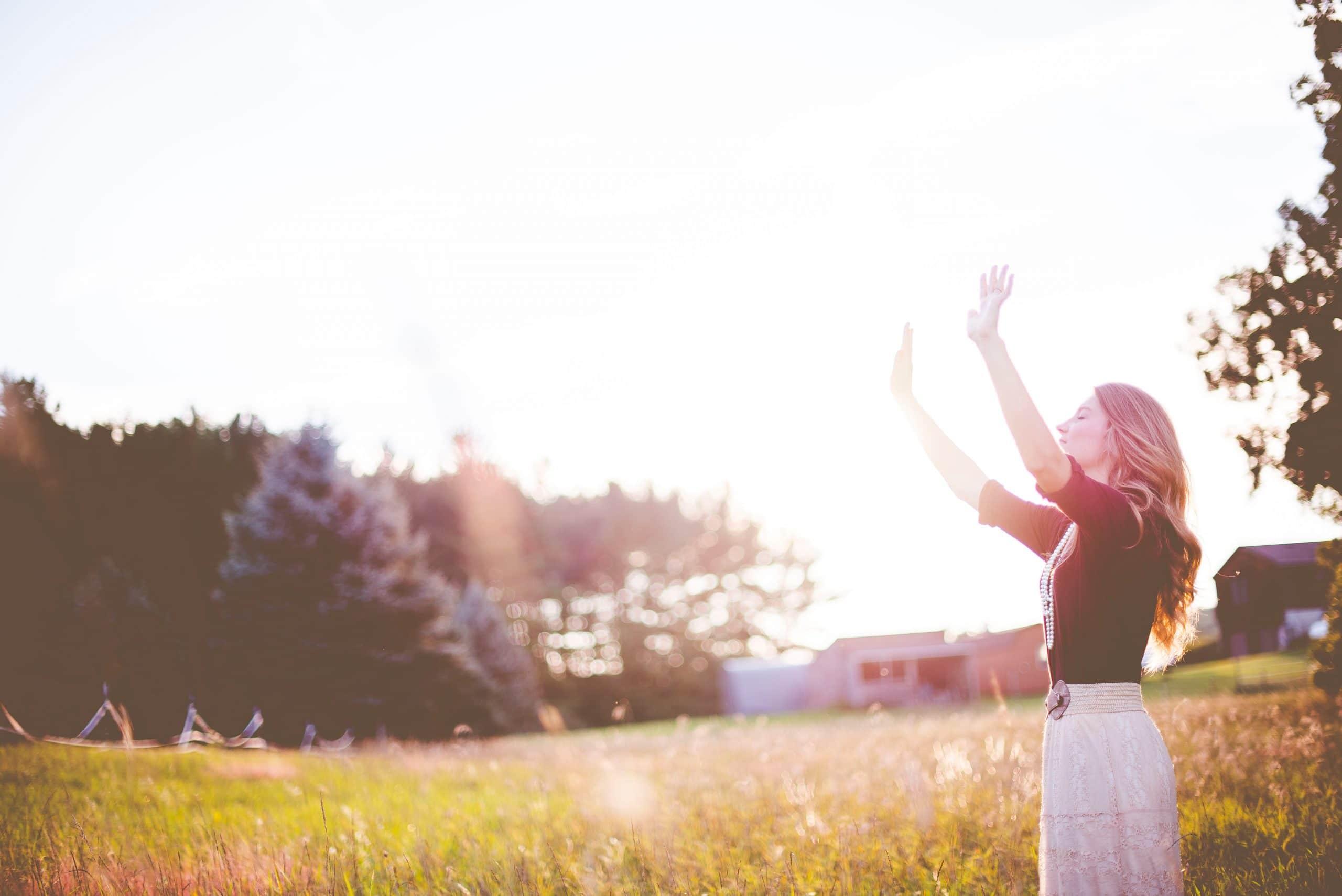 Mulher em campo com os braços para cima sendo iluminada pelo sol