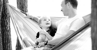 Pai e filho sentados em uma rede. O menino olha para o pai e ambos sorriem. A imagem é em preto e branco.