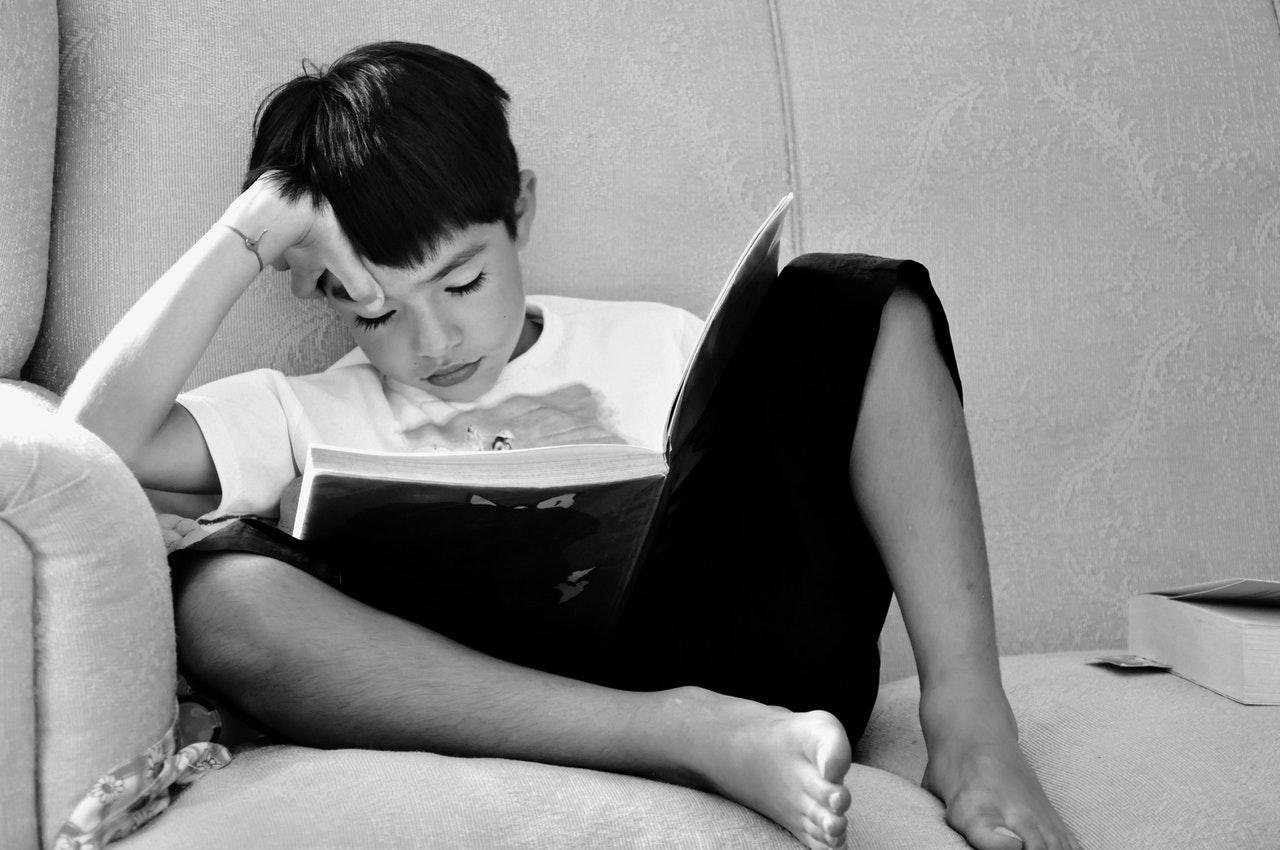 Menino sentado no sofá lendo livro em preto e branco