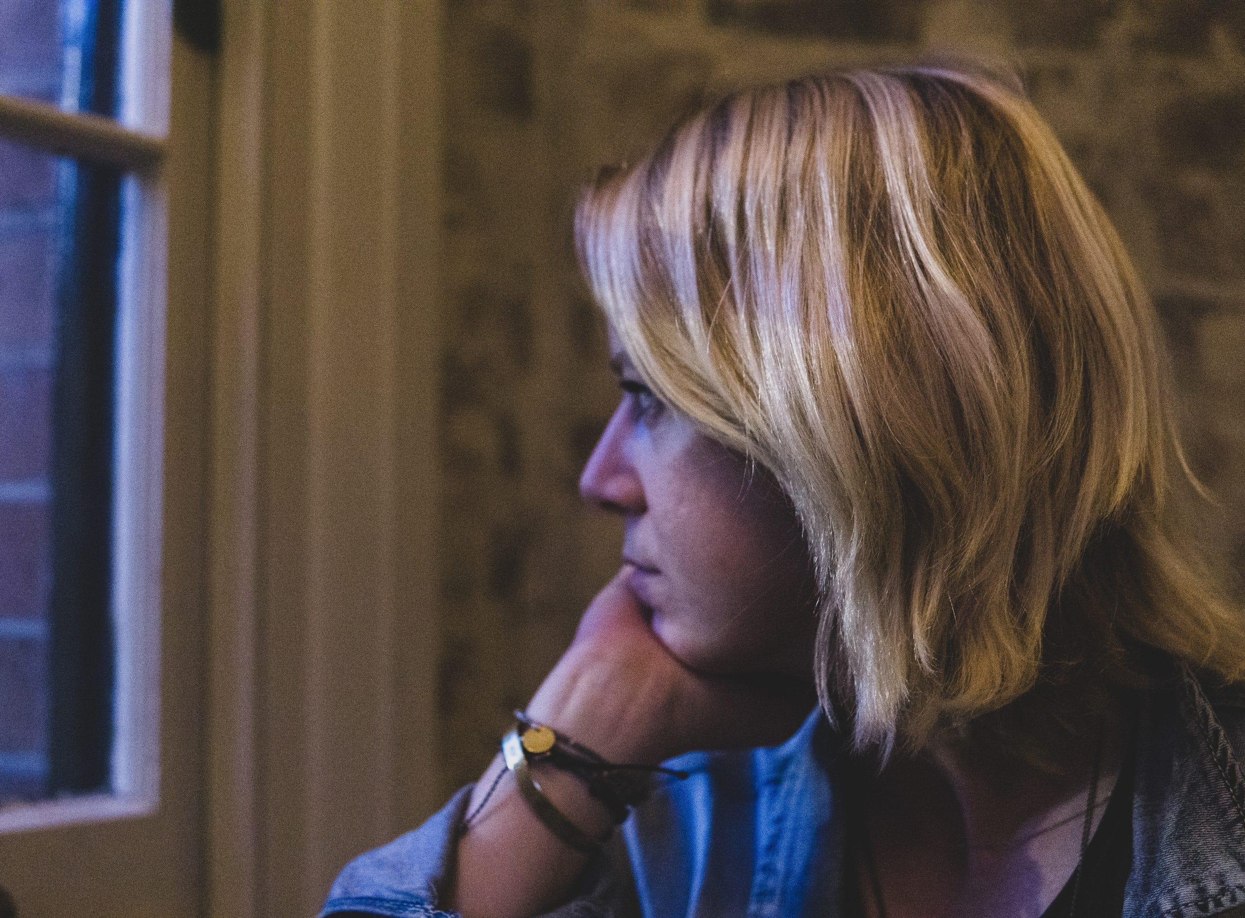 Mulher pensando olhando para a janela com expressão séria.