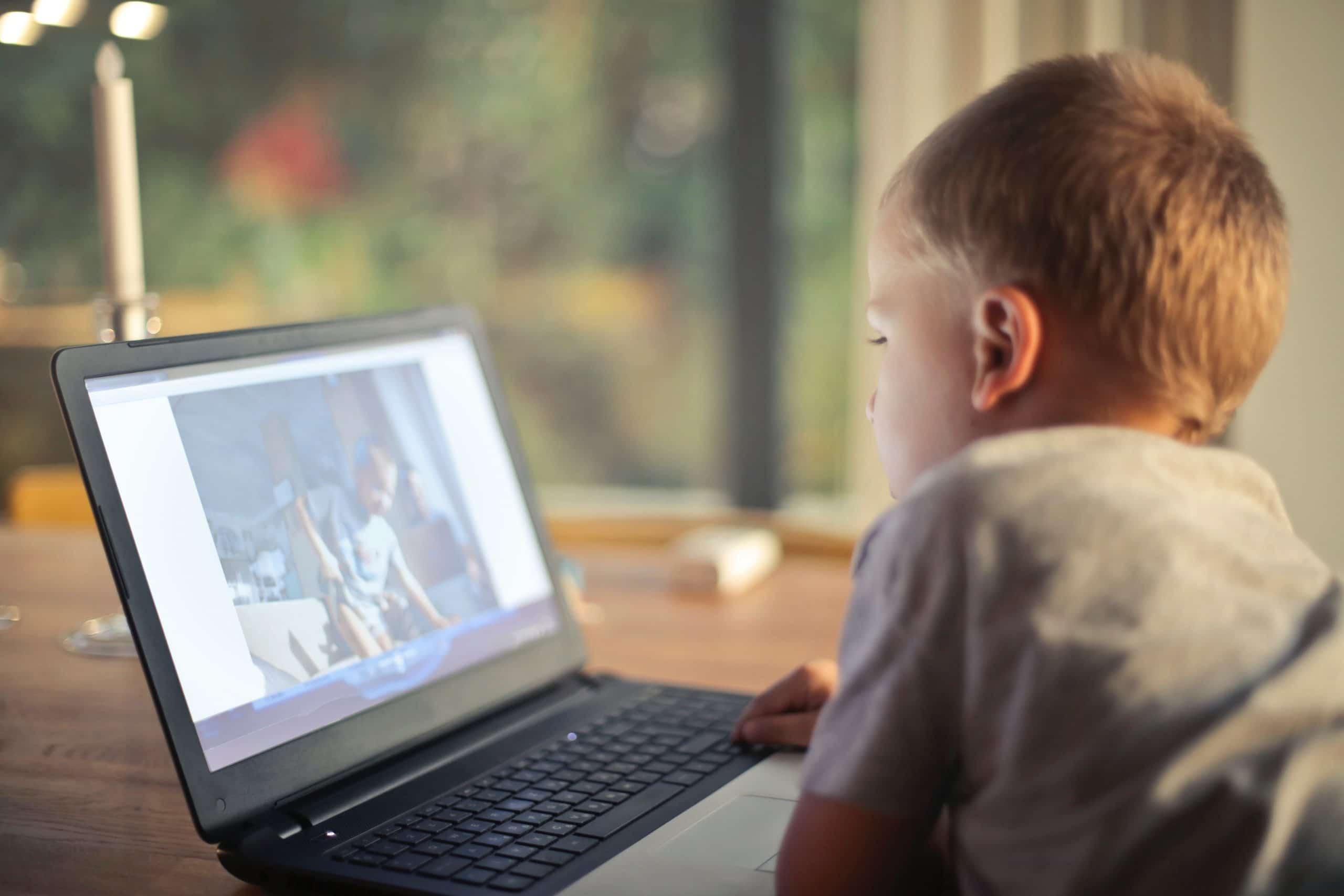 Criança usando o notebook para ver fotos.