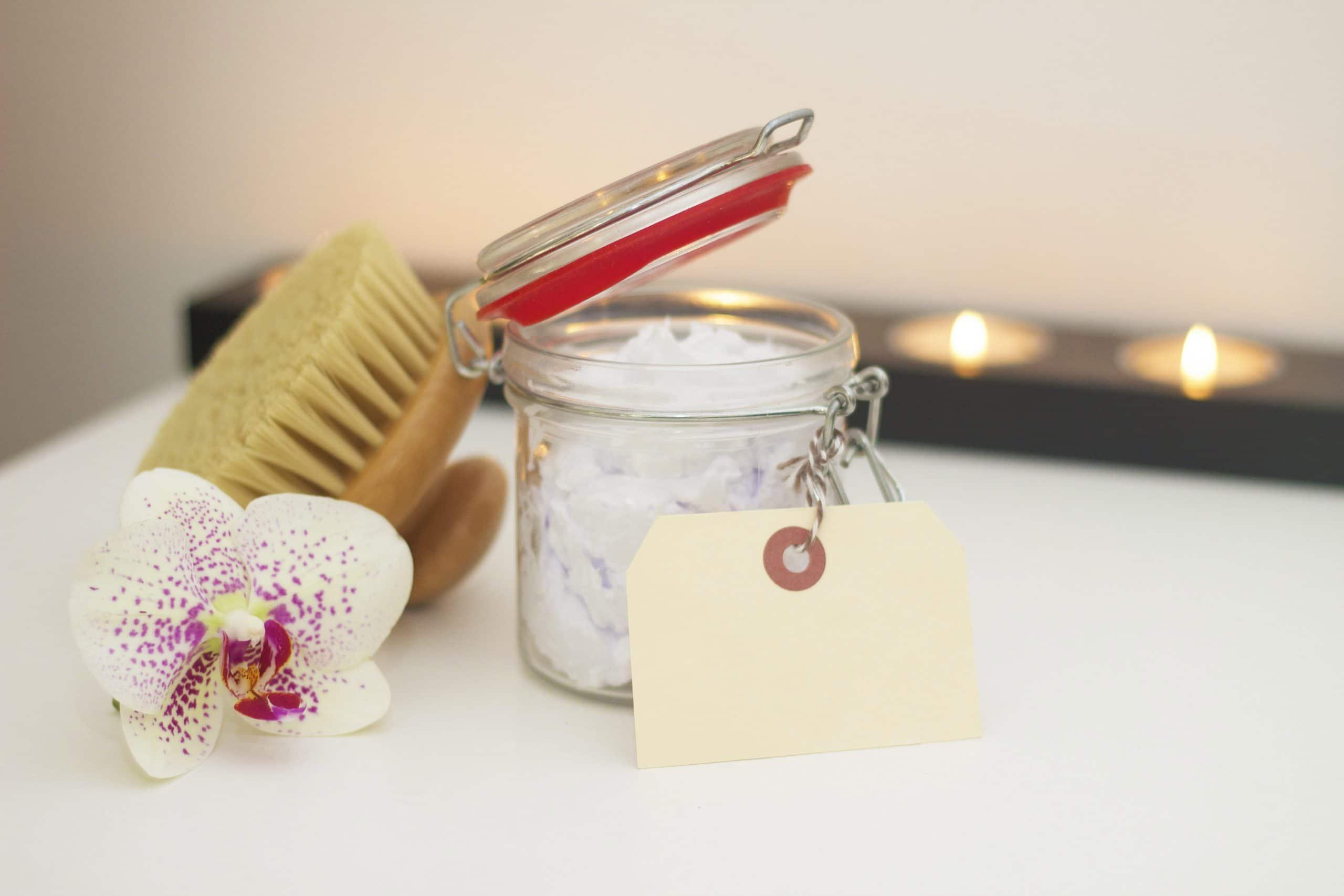 Mesa com uma flor, uma escova e um pote delicado com uma etiqueta em branco. Atrás, algumas velas acesas.
