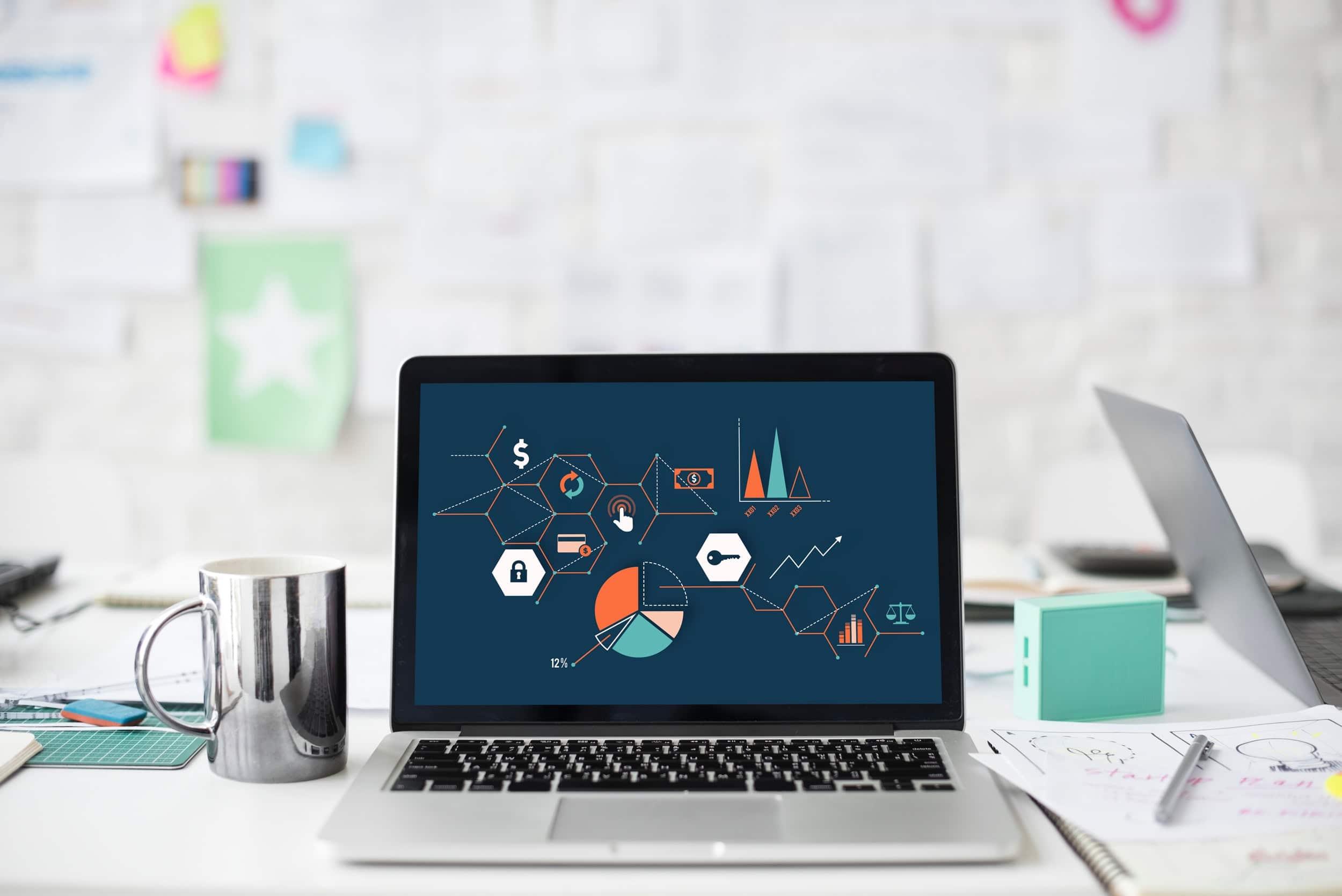 Laptop aberto em cima de uma mesa, rodeado por elementos de escritório. Na tela, aparecem gráficos e ilustrações.