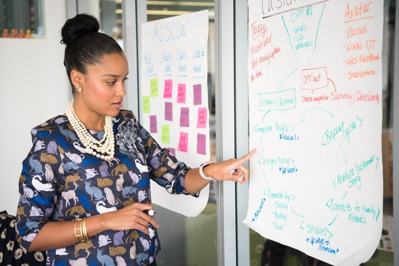 Mulher apontando anotação em papel de apresentação em sala de reunião
