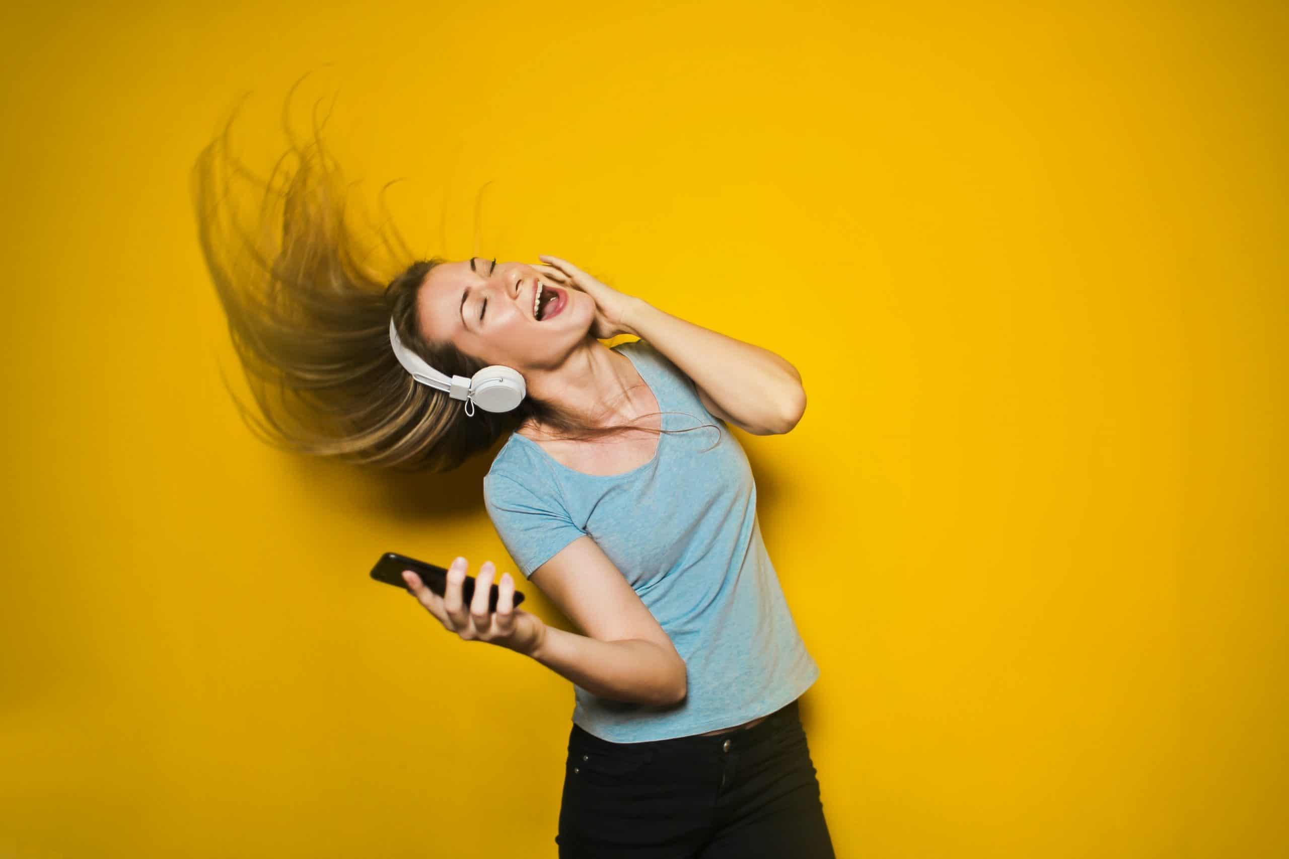 Mulher com celular na mão e fones de ouvidos jogando o cabelo com fundo amarelo