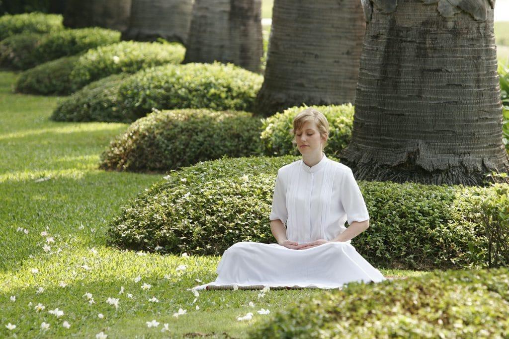 Menina sentada em posição de meditação em um jardim verde. Ela está em processo de auto cura.