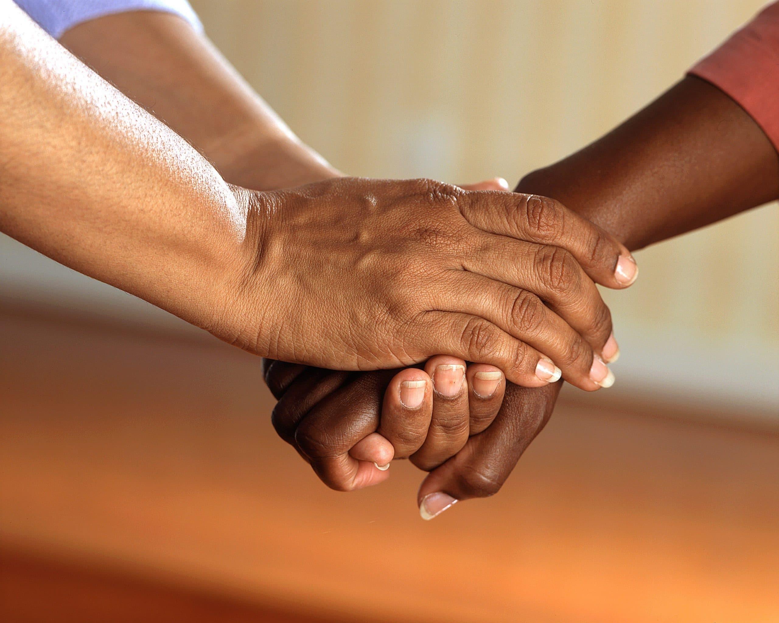 Mãos de duas pessoas unidas em sinal de gentileza.