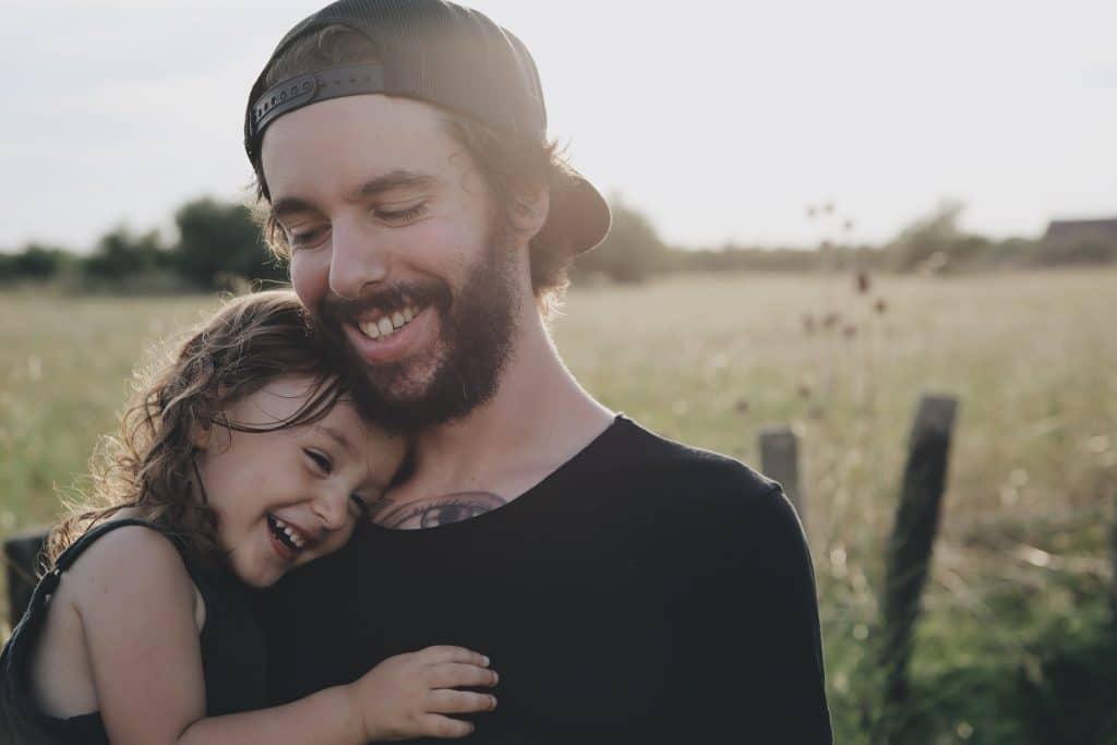 Um homem sorrindo enquanto segura uma menininha no colo. Ela está encostada nele e também está sorrindo.