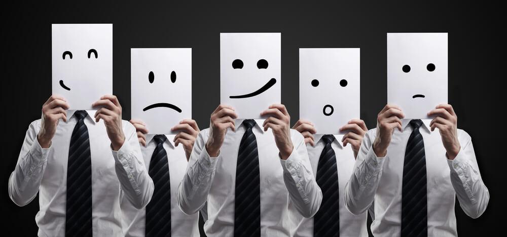 Cinco homens vestindo roupas sociais, com camisa branca e gravata preta, em pé formando uma fila, todos segurando folhas de papel brancas, cada uma com uma expressão facial diferente desenhada