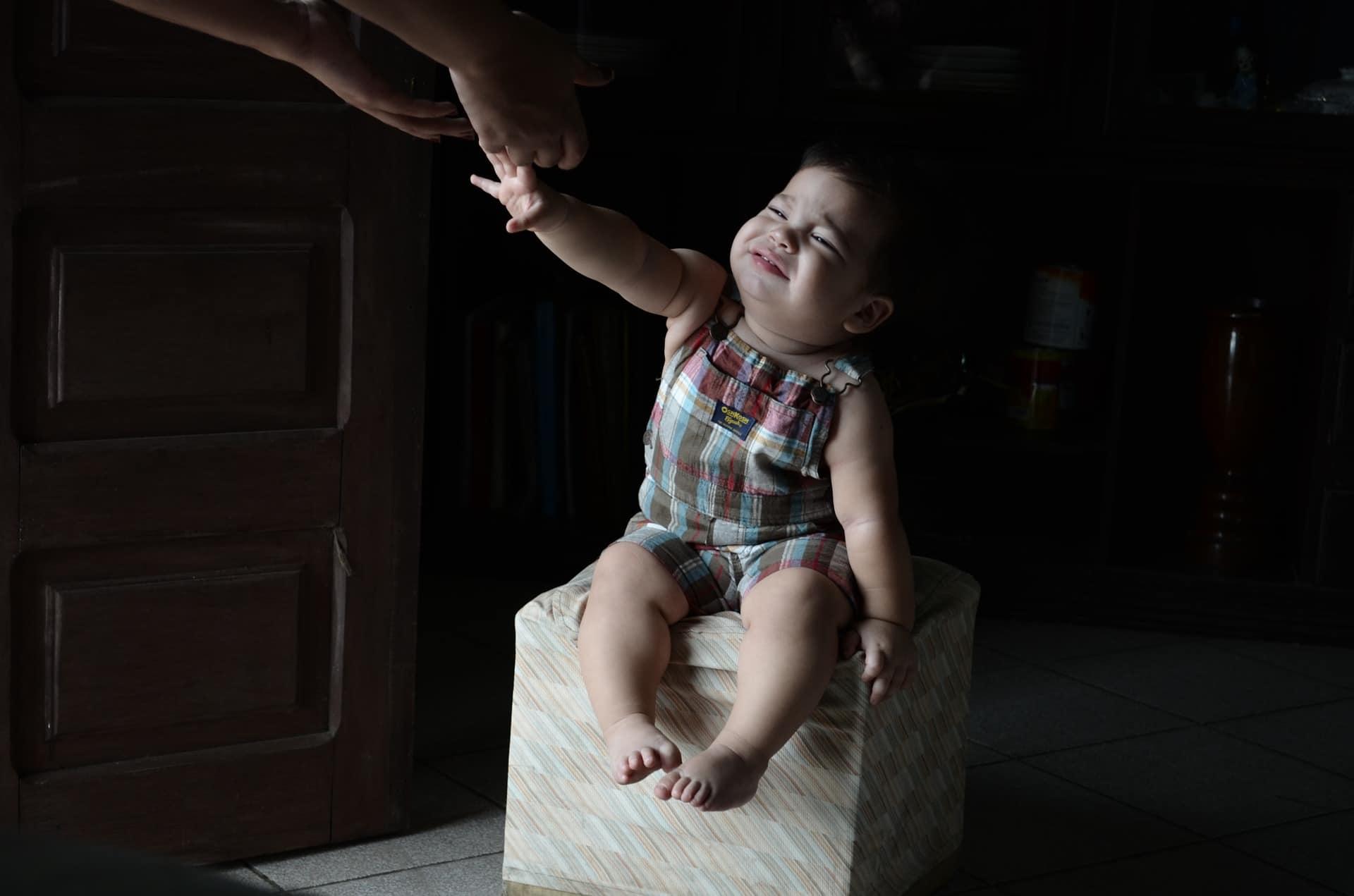 Crianças sentada chorando e esticando os braços para alguém.