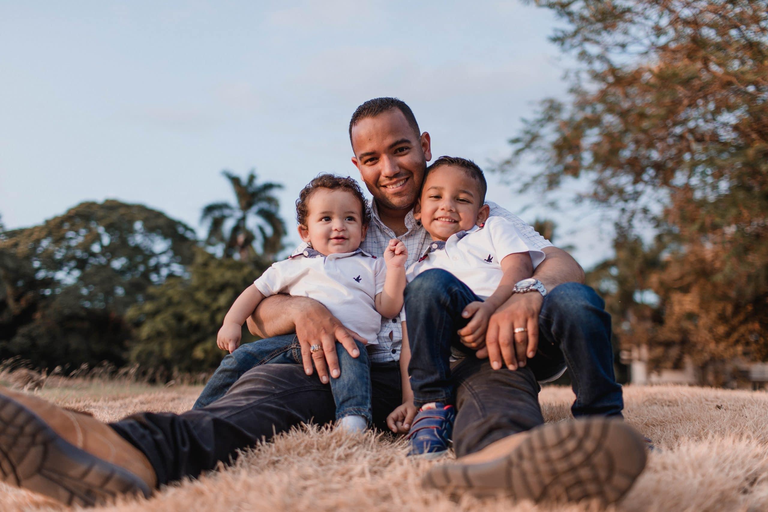 Pai segura seus dois filhos no colo, os três sentados na grama em um campo aberto. Todos sorriem.