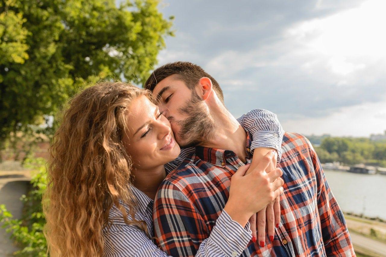 Casal abraçado com mulher abraçando o pescoço por trás e homem dando beijo no rosto