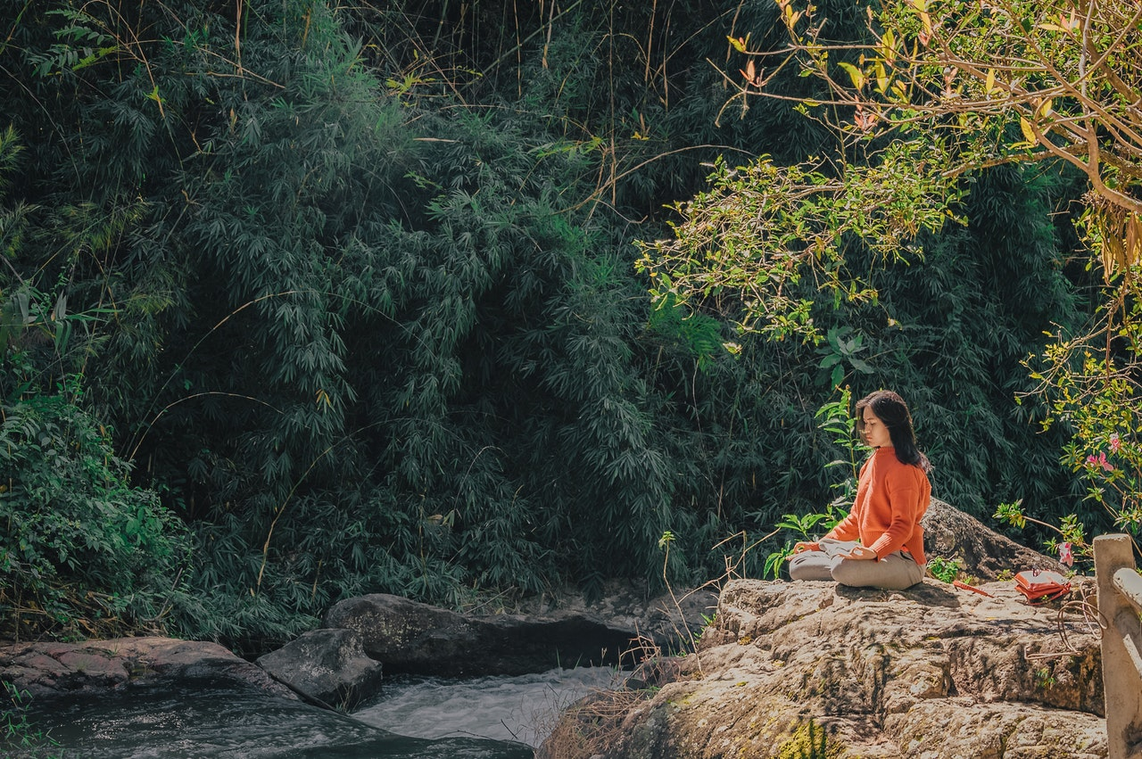 Mulher meditando em cima de uma pedra com floresta ao fundo