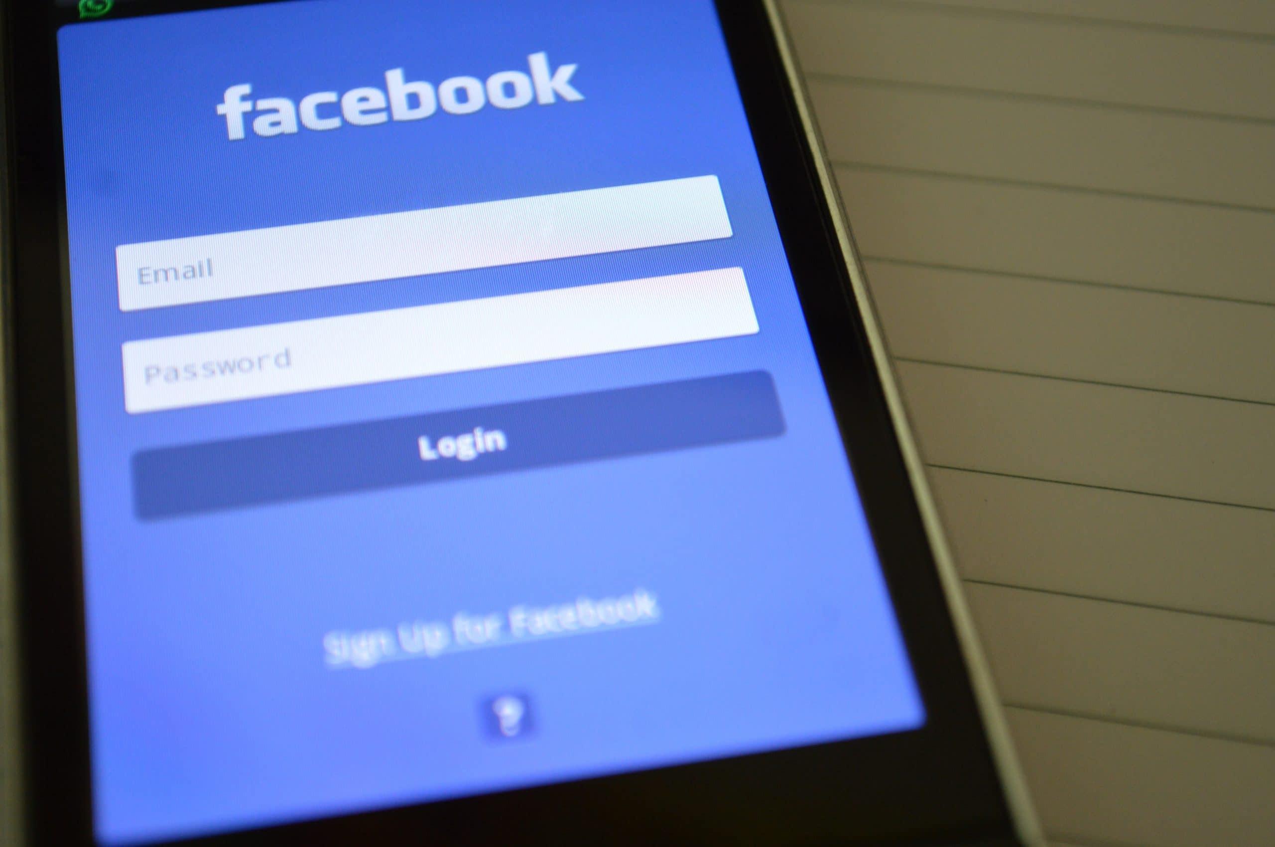 Celular aberto na tela de login do Facebook.