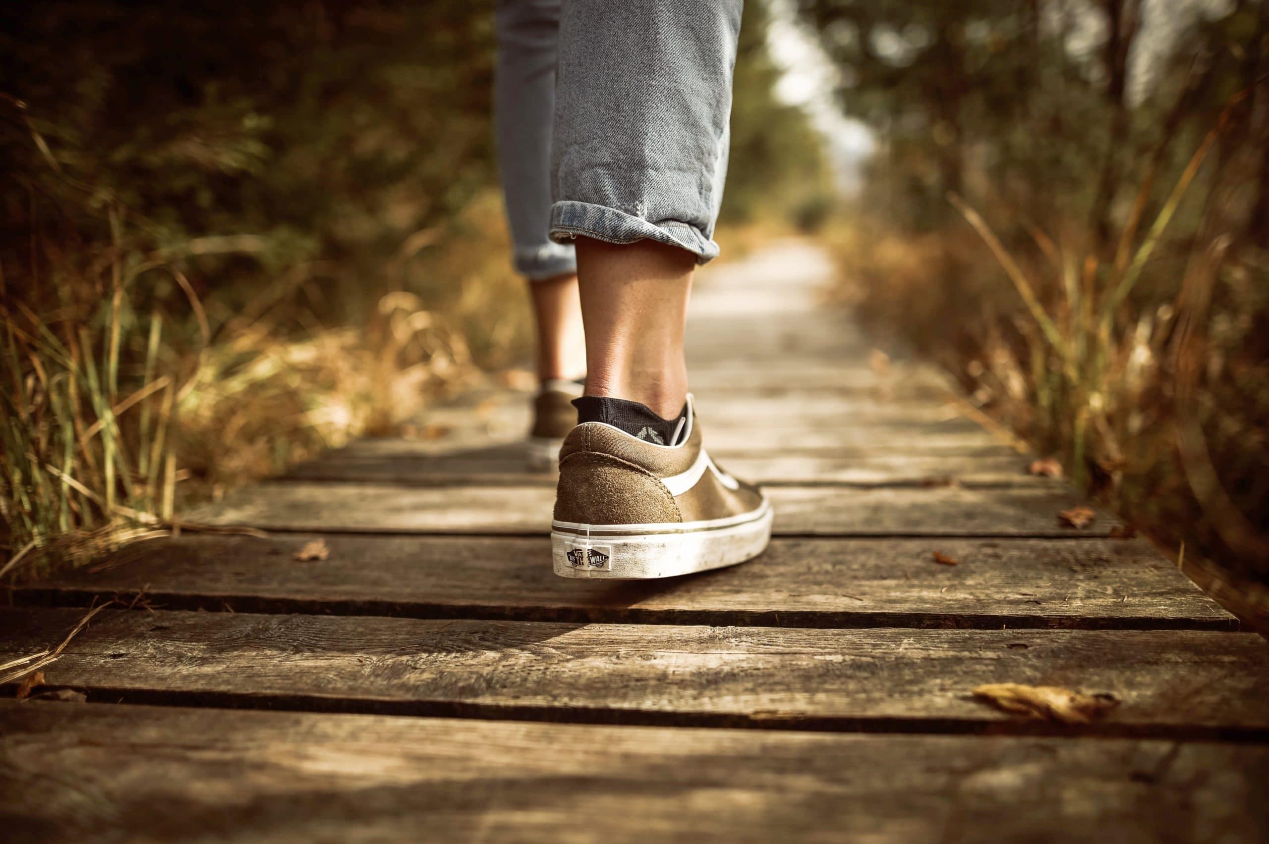 Pés andando sobre um caminho de madeira cercado pela natureza.