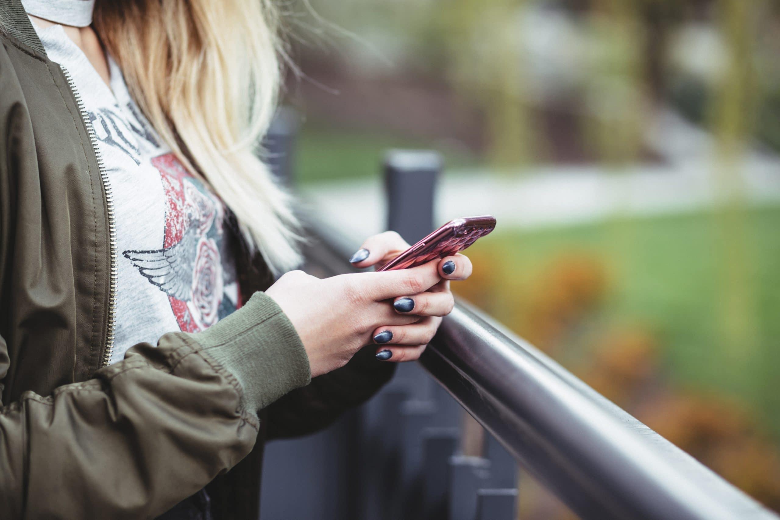 Mãos de mulher segurando celular na altura do peito