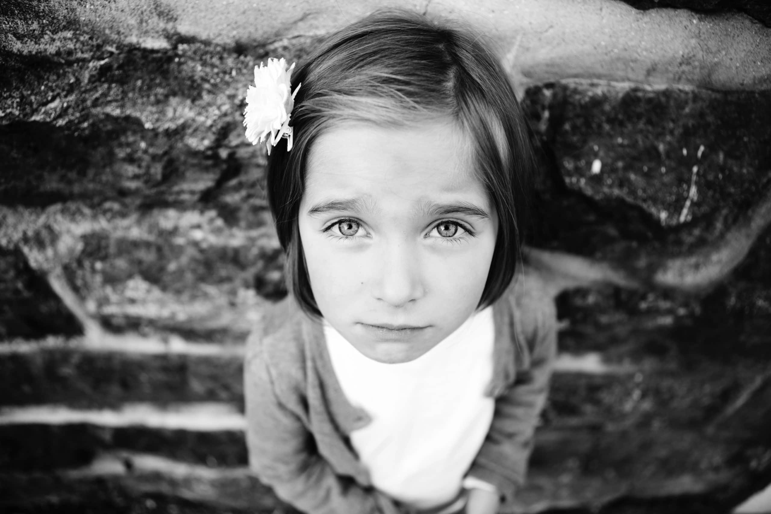 Menina vista de cima olhando para cima com rosto chateado