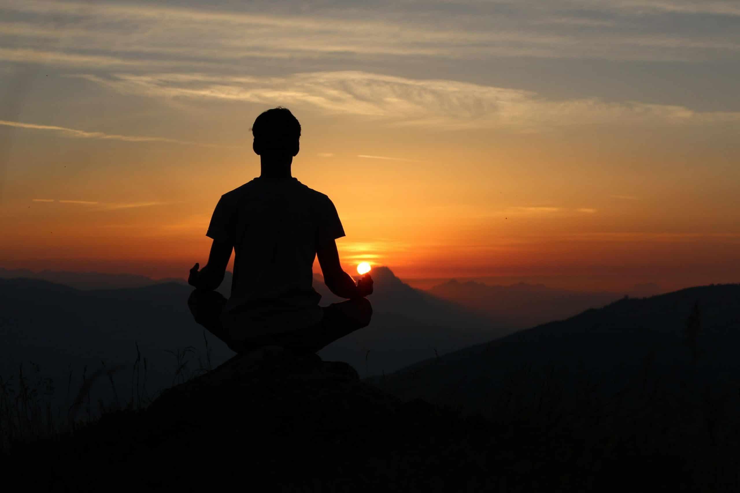 Silhueta de homem meditando no topo de uma montanha com pôr-do-sol ao fundo