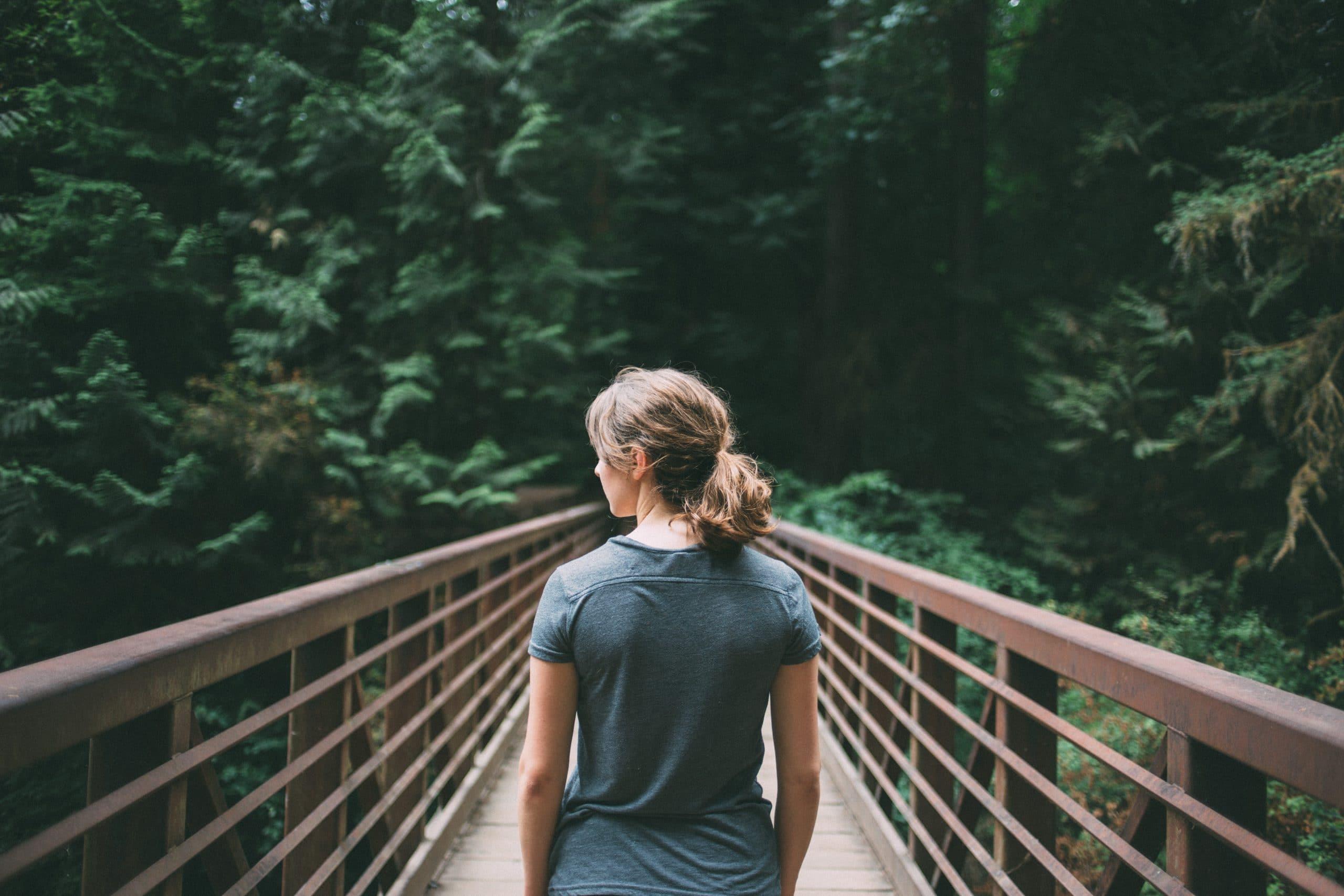 Mulher de costas em ponte de madeira com fundo de folhas verdes