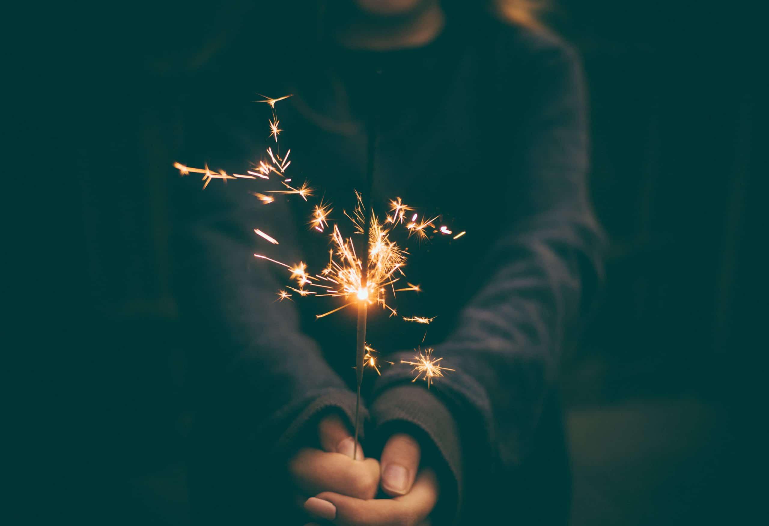 Mãos de moletom segurando vela de faísca queimando