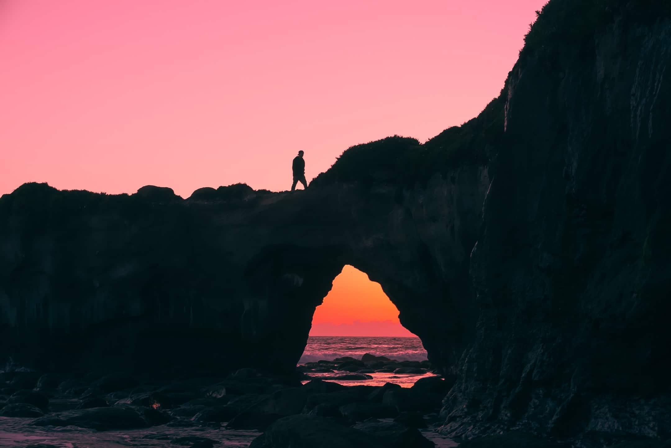 Homem caminhando em montanha com céu ao entardecer ao fundo