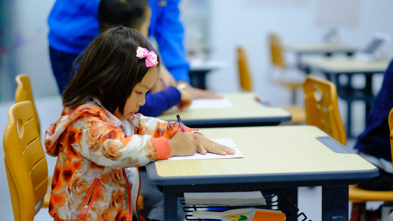 Criança pequena sentada em mesa da escola escrevendo em caderno