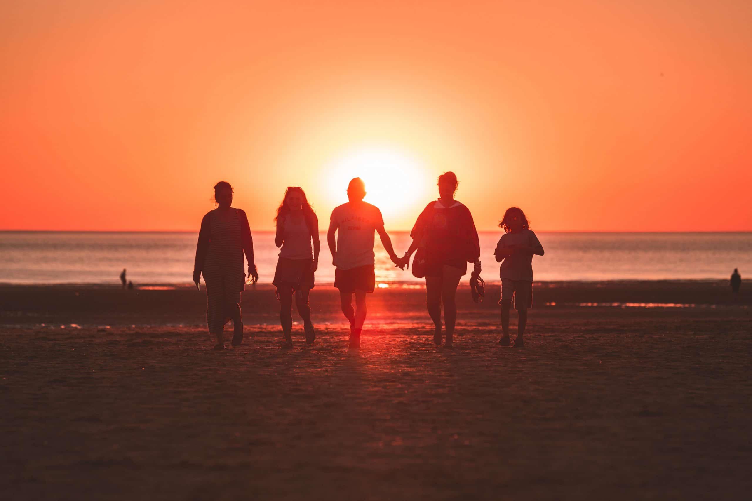 Silhueta de família voltando do mar com pôr-do-sol de fundo