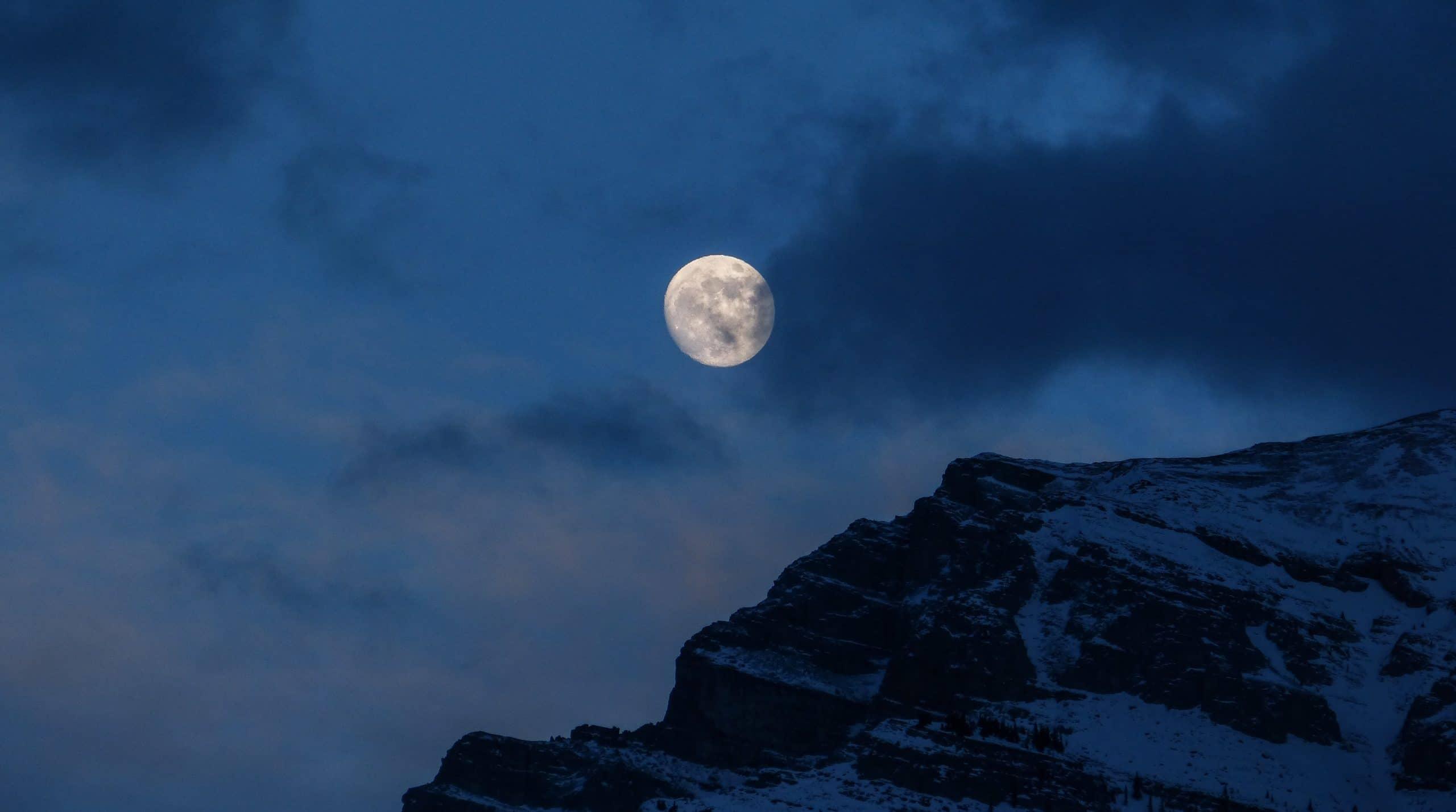 Lua cheia no topo de uma montanha nevada.