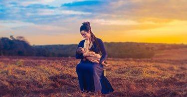 Mãe amamentando seu filho em um campo aberto. Ela está vestindo um vestido roxo e ao fundo há uma linda paisagem de entardecer.