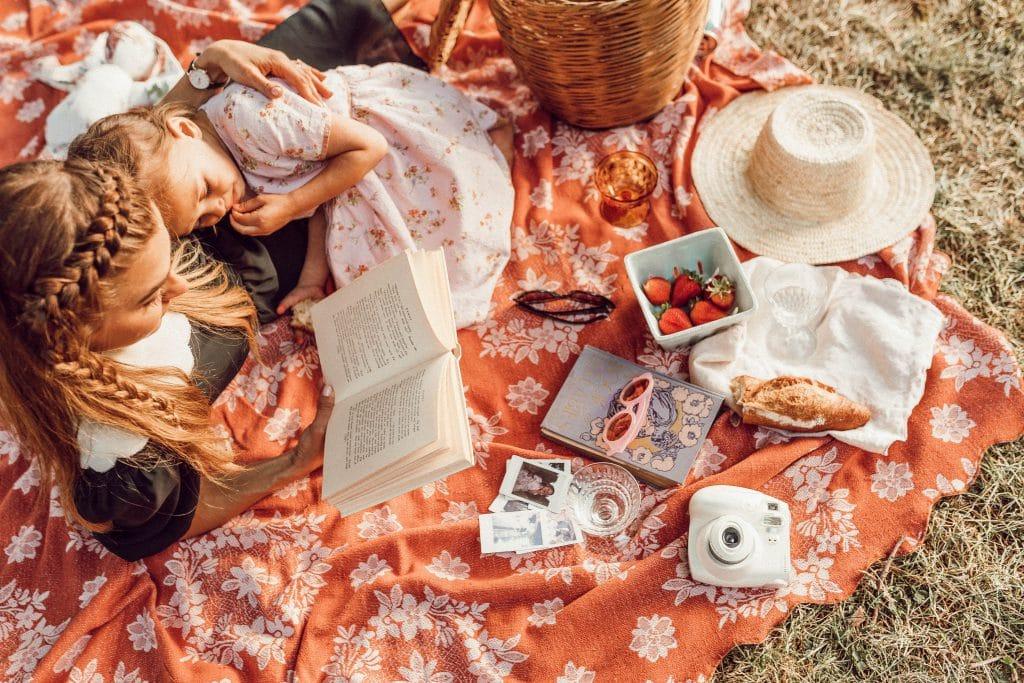 Mãe com sua filha deitada em uma toalha de piquenique enquanto lê um livro.
