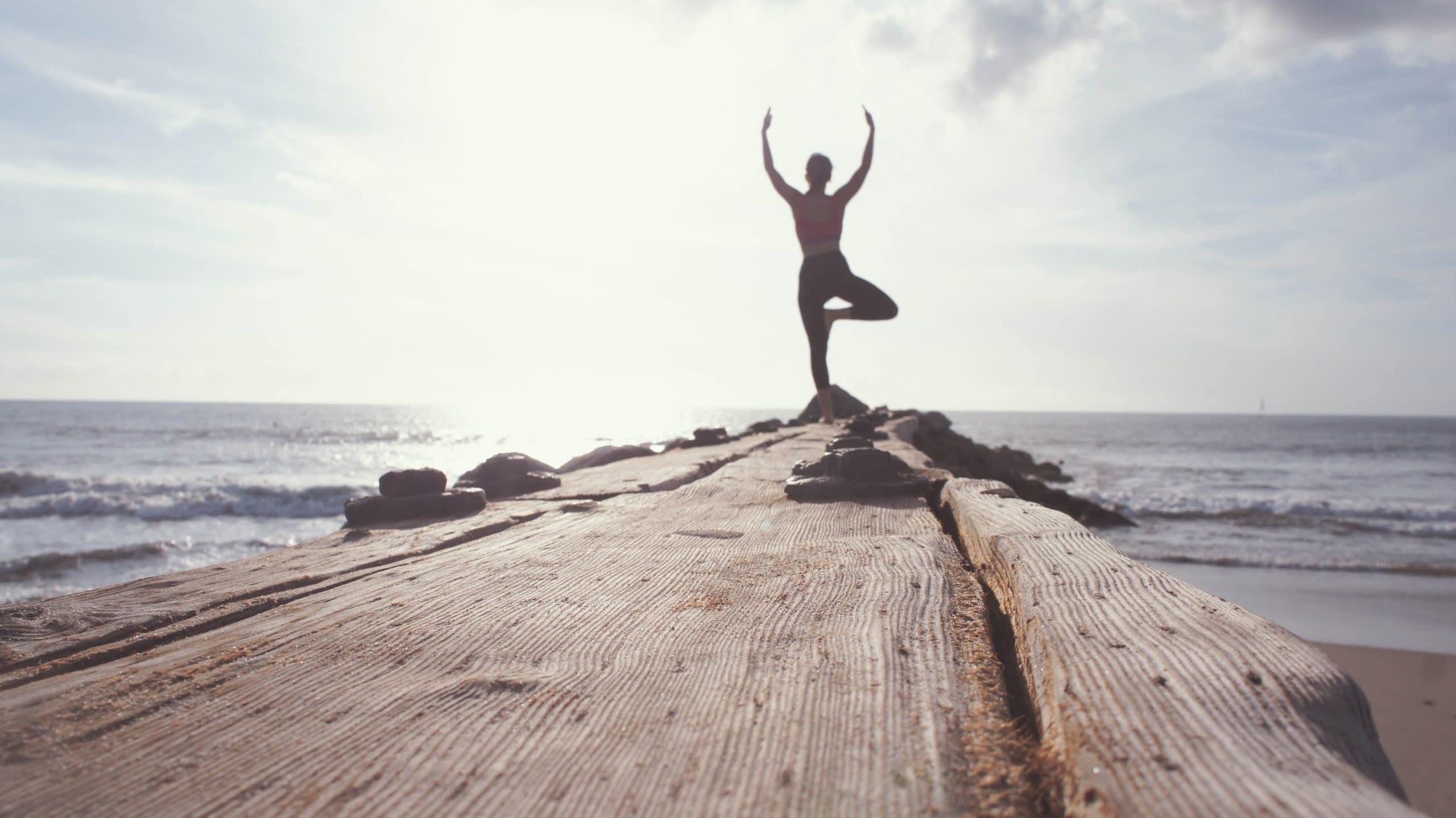 Mulher de costas em posição de ioga em ponte com fundo de céu e mar