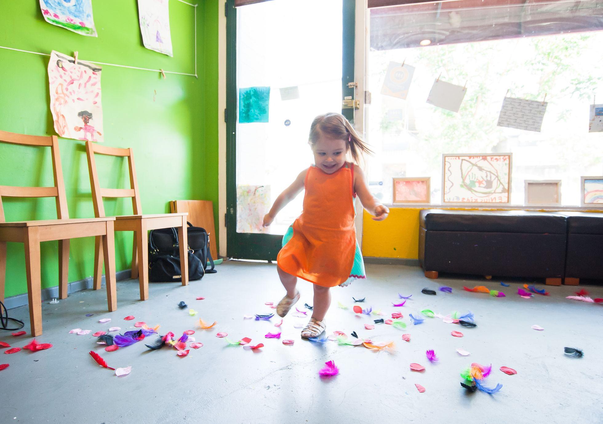 Criança brincando na escola com avental e papeis coloridos pelo chão