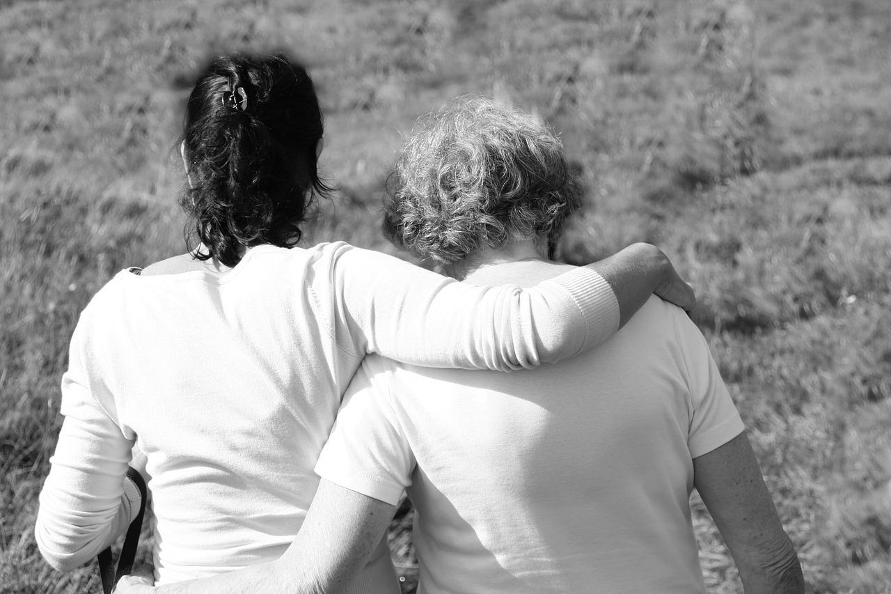 Duas mulheres, uma mais nova e outra mais velha, abraçadas de costas em um campo. A imagem está em preto e branco.