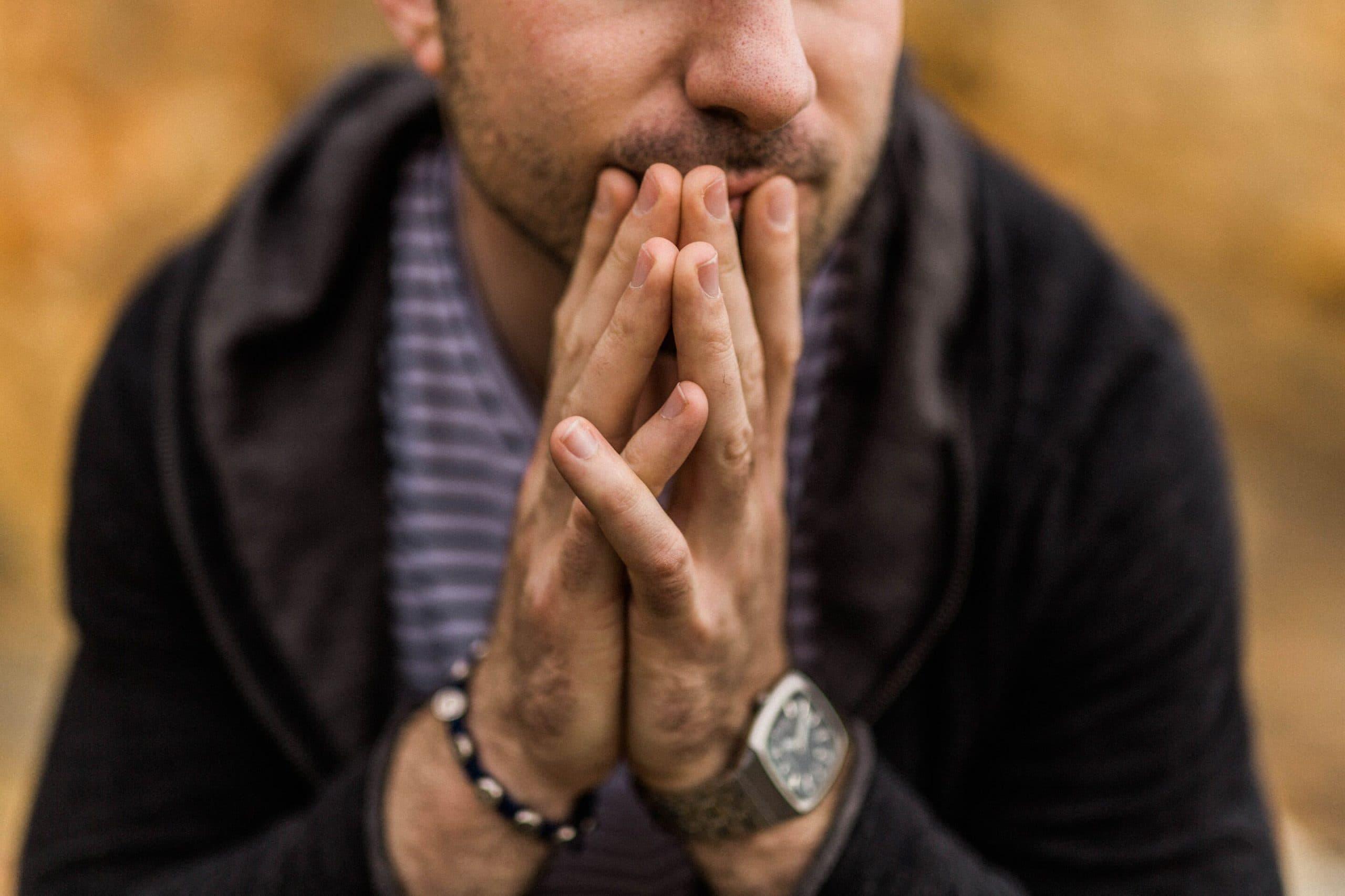 Homem no foco com metade do rosto aparecendo e mãos apoiadas no queixo pensativo