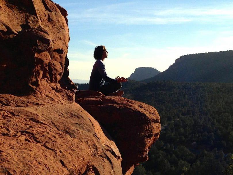 Mulher sentada sobre uma rocha em posição de meditação representando o eu sem fronteiras.