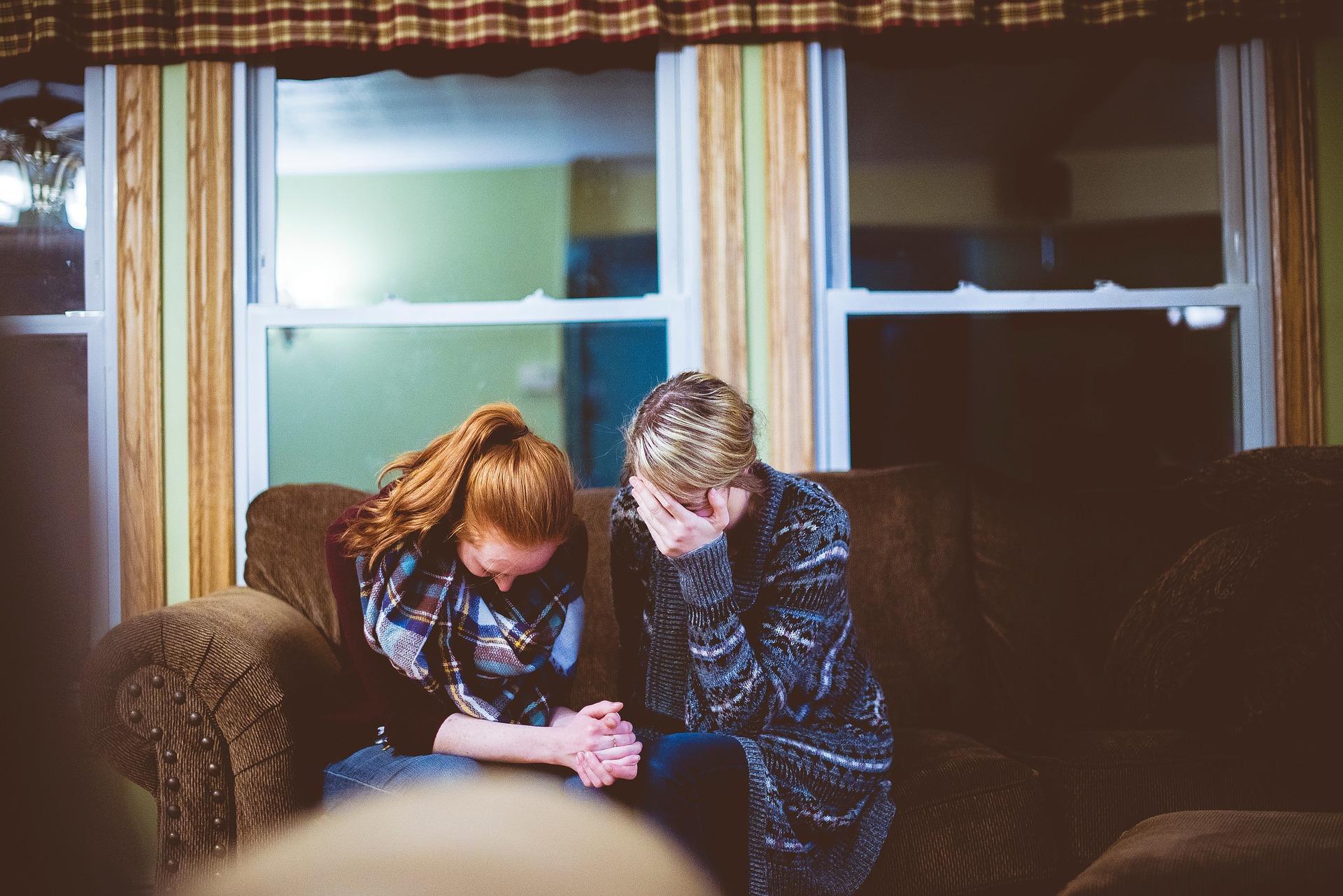 Duas mulheres chorando sentadas em um sofá com os rostos abaixados e as mãos cobrindo-os.