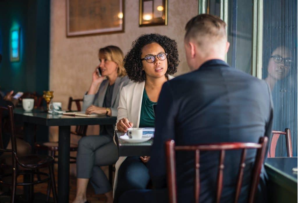 Mulher negra e Homem branco, sentados em uma mesa de restaurante. Mulher esta com uma expressão de brava olhando para o homem.