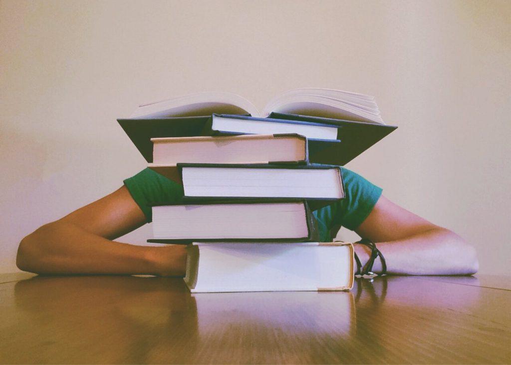 Pessoa sentada em uma mesa, se apoiando atras de uma alta pilha de livros.