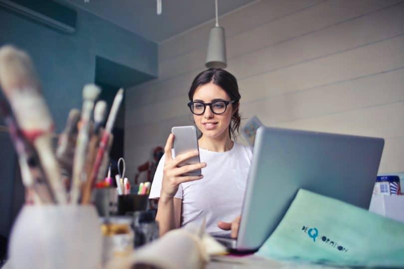 Mulher sorridente, sentada em uma mesa de escritório, olhando para o seu celular, com seu notebook aberto e funcionando.