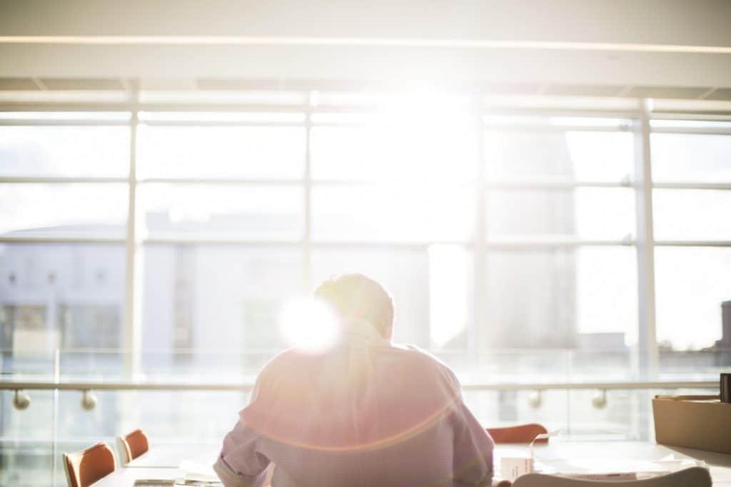 Homem vestindo roupas sociais, sentado em uma mesa de reuniões, em frente à uma janela onde o sol está batendo.
