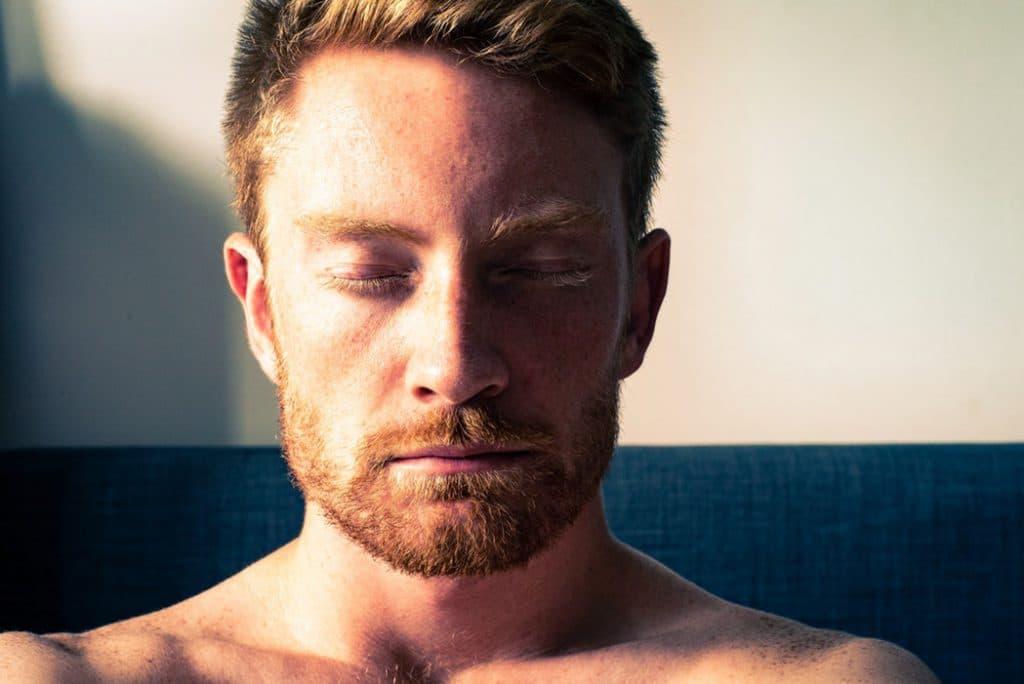 Homem sentado em um sofá, com os olhos fechados, meditando