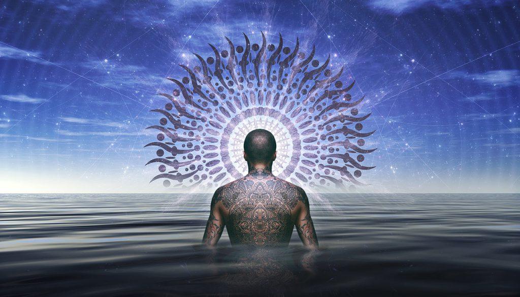 Homem de costas no mar. Ele tem as costas tatuada. À frente dele está uma mandala e o céu azul.